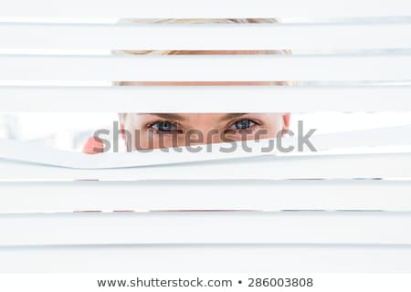 Nosy blond peering through window blinds Stock photo © photography33