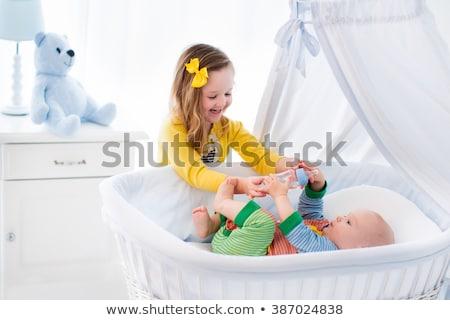 Toddler girl giving bottle of milk to baby sister stock photo © lunamarina