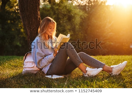 Smiling girl with backpack reading book Stock photo © deandrobot