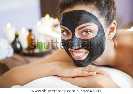 Stock photo: Young woman with a mask for the face of the therapeutic black mu