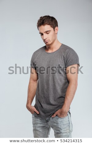 sad upset young man in hat standing and looking down stock photo © deandrobot