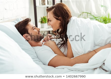 boldog · álmos · nő · ágy · mosolyog · fiatal - stock fotó © dolgachov