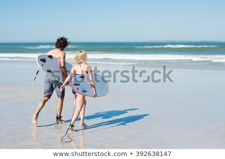 rear view of man carrying surfboard while running on sand stock photo © wavebreak_media