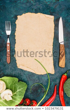 top view of blank parchment fork with knife and raw vegetables on black stock photo © lightfieldstudios