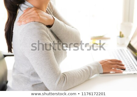 Young woman suffering from pain in shoulder Stock photo © eddows_arunothai