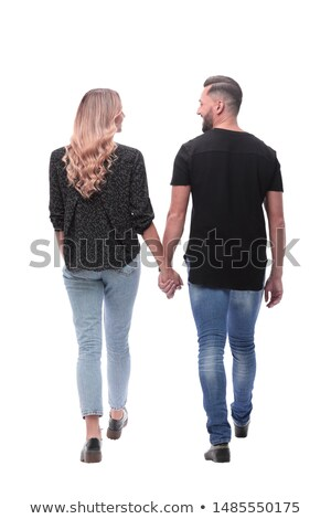 Back view of smiling young couple holding hands Stock photo © deandrobot