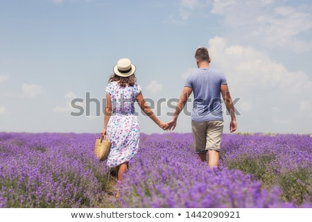 Couple walking in the lavender field outdoors holding hands of each other. Stock photo © deandrobot