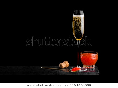 elegant glass of yellow champagne with red caviar on golden spoon on marble board on black backgroun stock photo © denismart