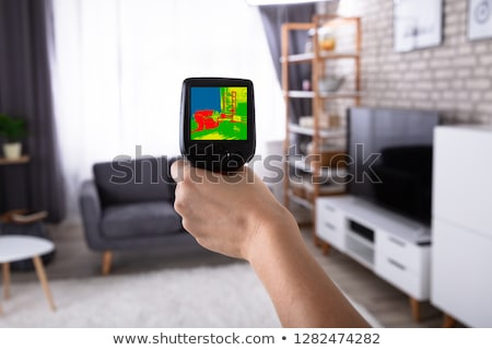 Woman Using Infrared Thermal Camera In Living Room Stock photo © AndreyPopov