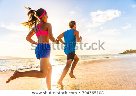 Fitness running couple exercising cardio on beach. Stock photo © Lopolo