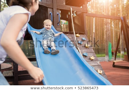 Funny toddler boy having fun on slide on playground Stock photo © galitskaya