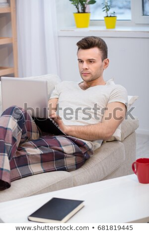 Young man with laptop computer on a comfortable couch at home Stockfoto © Lopolo