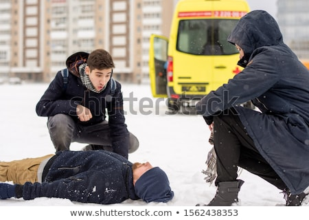 Two guys sitting on squats by sick or unconscious young man lying in snow Stock photo © pressmaster
