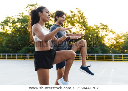 Photo of athletic happy couple doing exercises while working out Stock photo © deandrobot
