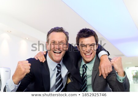 Horizontal shot of happy businessman looks cheerfully and confidently aside, keeps hands in pockets, Stock photo © vkstudio