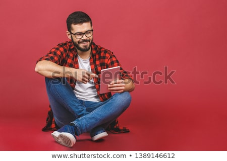 A smiling man sitting on the floor with a tablet, isolated on wh Stock photo © dacasdo