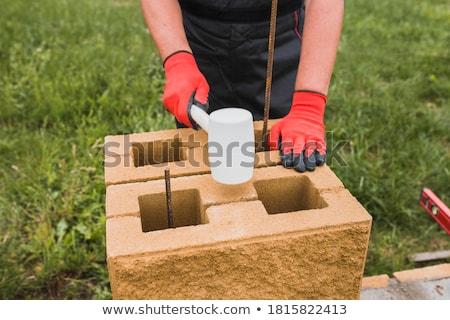Mason knocking bricks into place with hammer Stock photo © photography33