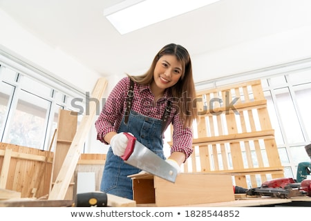 A female carpenter with a handsaw. Stock photo © photography33