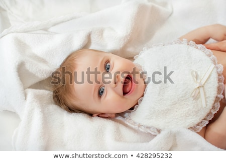 baby girl with toothache in pink with on white fur Stock photo © lunamarina