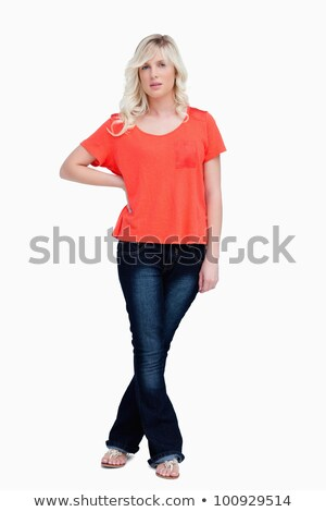Serious fair-haired teenager standing with her legs crossed against a white background Stock photo © wavebreak_media