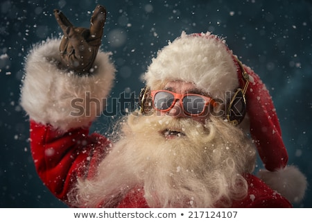 Santa Claus is listening to music in headphones outdoors at Nort Stock photo © HASLOO
