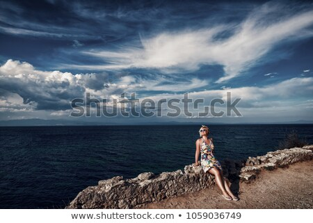sitting smiling beautiful woman on stone seacoast Stock photo © Paha_L
