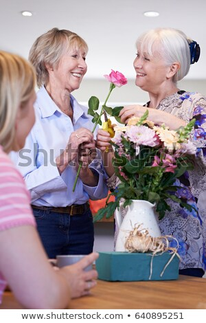 mature woman arranging flowers in vase. Stock photo © IS2