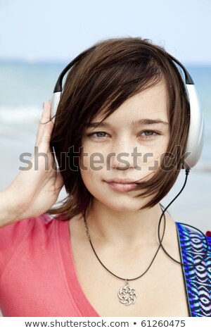 Young brunet girl with headphone and guitar on the beach. Stock photo © Massonforstock