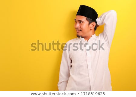 cheerful young asian man standing isolated over yellow background using mobile phone showing thumbs stock photo © deandrobot