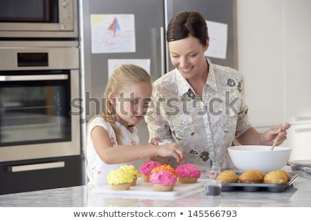 Stok fotoğraf: Happy Mother And Daughter Baking Cupcakes At Home