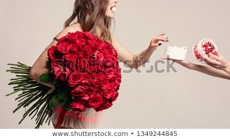 Beautiful lady with red roses taking a sweet from a box. Stock photo © studiolucky