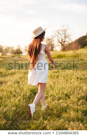 Stock photo: Photo from back of european teen lady with long dark hair wearin