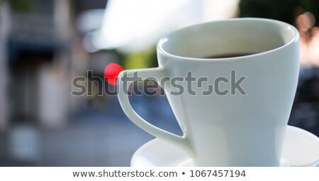 Coffee cup and saucer against blurry street Stock photo © wavebreak_media
