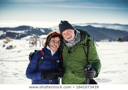 Active female hiker with trekking sticks looking at husband with camera on trip Stock photo © pressmaster