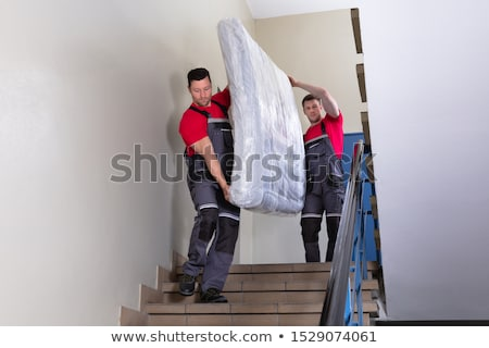 Two Male Movers Walking Downward With Furniture On Staircase Stock photo © AndreyPopov