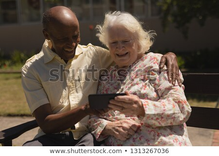 Foto d'archivio: Front View Of Happy Senior Couple Sitting On Bench And Using Laptop On Sunny Day In Garden