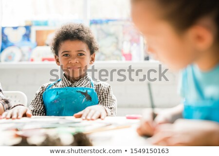Cute schoolboy of African ethnicity in blue apron sitting by desks at lesson Stock photo © pressmaster