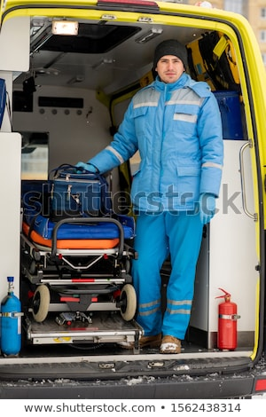 Male paramedic with first aid kit standing by stretcher in ambulance car Stock photo © pressmaster