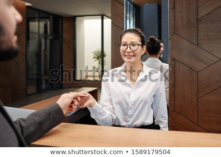 Young Asian female receptionist passing card from hotel room to businessman Stock photo © pressmaster
