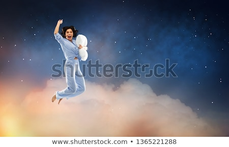 happy woman in pajama jumping with pillow over sky Stock photo © dolgachov
