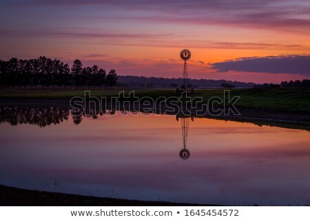 Sunrise over dam with wind mill in rural Australia Stock photo © lovleah
