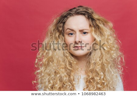 Young attractive woman has discontent expression, raises eyebrow in bewilderment, being dissatisfied Stock photo © vkstudio