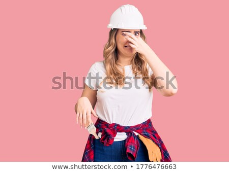 Disgusted woman holding a paintbrush Stock photo © photography33