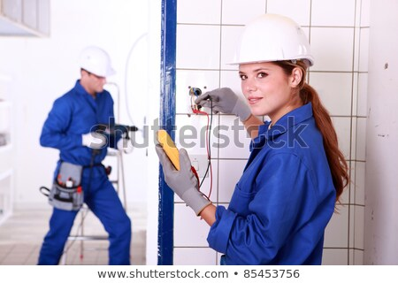 Foto stock: Grey  Haired Man Drilling Hole In Wall