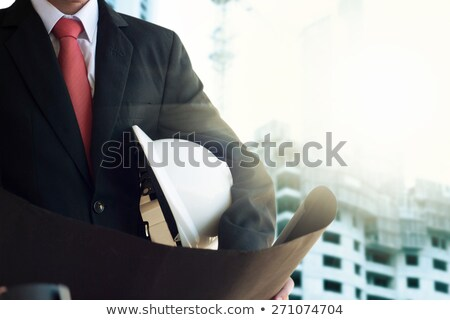 Foto stock: Businessman Holding Helmet And Blueprints