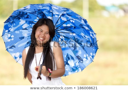 Beautiful young Thai girl under a blue sunshade Stock photo © smithore