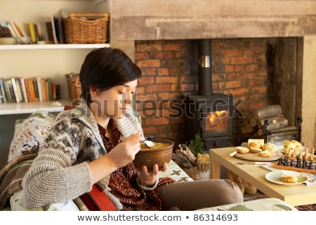 Stock fotó: Young Woman Having Tea By Fire
