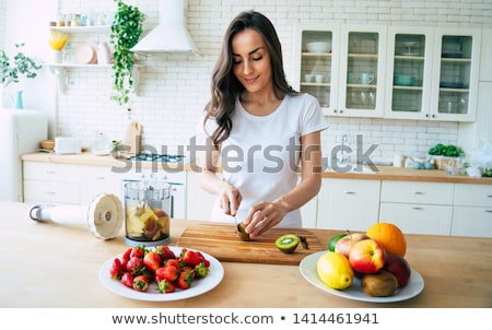 Stock photo: Young Woman Making Fruit Smoothie in Blender