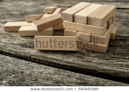 Blank wooden block leaning on a structure made of many other blo Stock photo © snowing