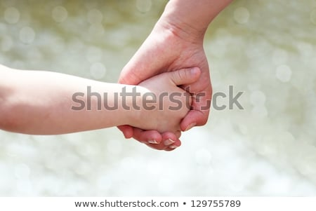 Mother holding childs hand in water Stock photo © IS2